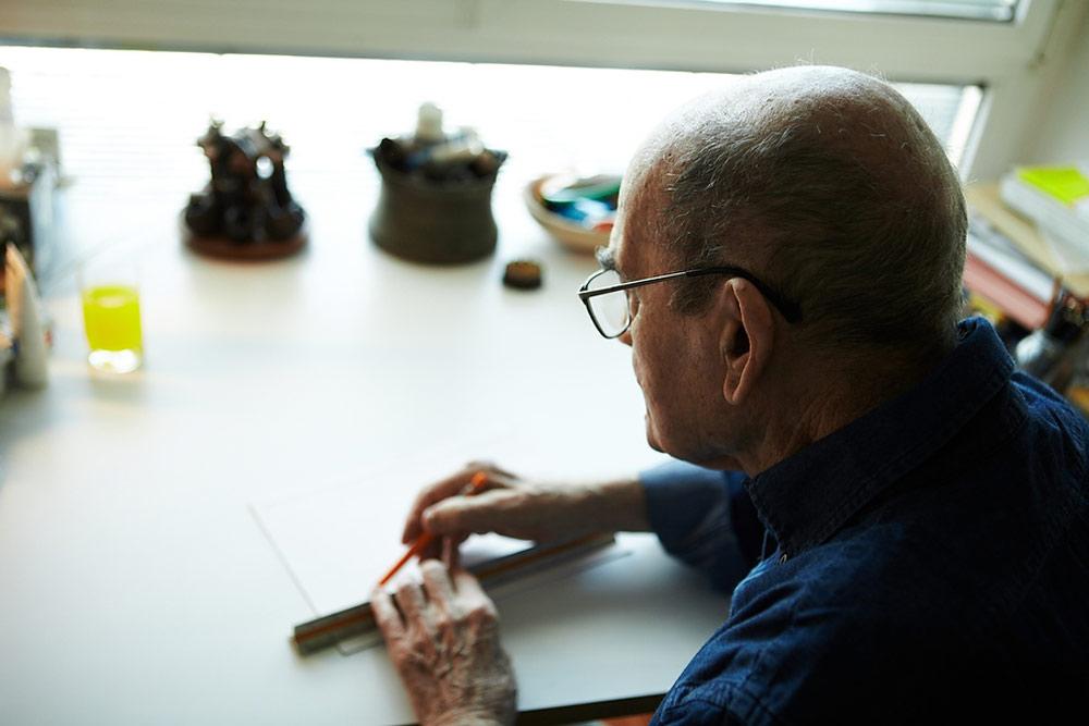 בדירתו במגדל האופרה בתל אביב, בראיון האחרון. גם כשהאט את הקצב, לא יכול היה להיפרד משולחן השרטוט (צילום: ניקיטה פבלוב)