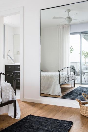על הקיר שמול היציאה למרפסת בחדר ההורים תלויה מראה ענקית המשקפת את הנוף וכמו מכניסה אותו פנימה (צילום: איתי בנית)