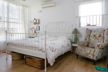 מיטת ברזל והרבה טקסטיל בחדר ההורים (צילום: שירן כרמל)