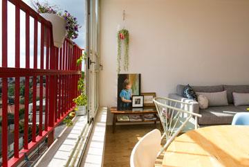 הצבע האדום של המעקה מייחד את בנייני השכונה. השולחן הקטן שליד הספה הוא ירושה מהסבתא (צילום: שירן כרמל)