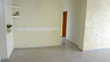 """הכניסה לדירה """"לפני"""". הסלון מימין, המטבח משמאל, והמסדרון מוביל לחדרי השינה (צילום: שירן כרמל)"""