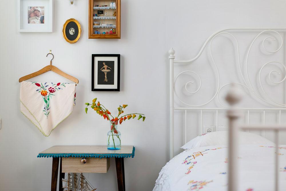 חדר השינה של ההורים. כיסוי המיטה הוא בן 70 שנה. גם הקישוטים שעל הקיר מבטאים את אהבתה של בעלת הבית לפריטים ישנים ולטקסטיל (צילום: שירן כרמל)