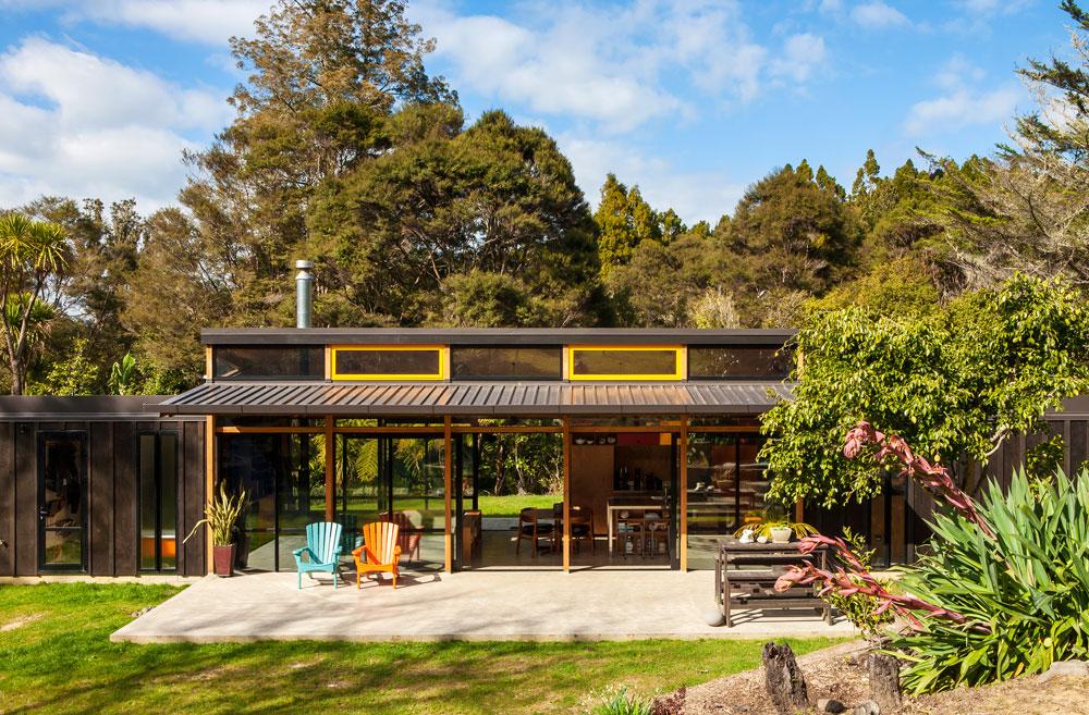 ביתה של משפחה ליד אוקלנד, בניו זילנד. מבנה ארוך וצר, שבמרכזו מטבח, פינת אוכל ופינת ישיבה בחלל פתוח עם קירות שקופים אל הטבע ותקרה גבוהה במיוחד. משני הצדדים אגפי השינה - האחד של ההורים, השני של הילדים (צילום: Emma-Jane Hetherington)
