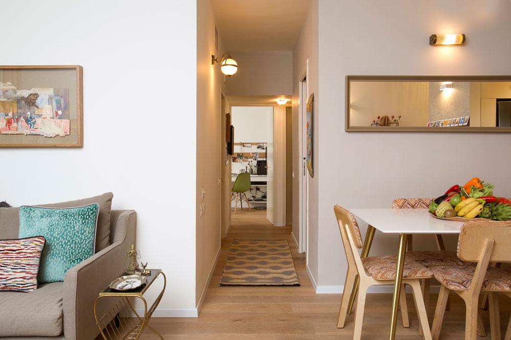 בין הסלון לפינת האוכל מפריד מסדרון שמוביל לשלושת חדרי השינה. בתחילתו תלויה עבודה של עדי סנד ובסופו נראית פינת העבודה שבחדר ההורים (צילום: שירן כרמל)