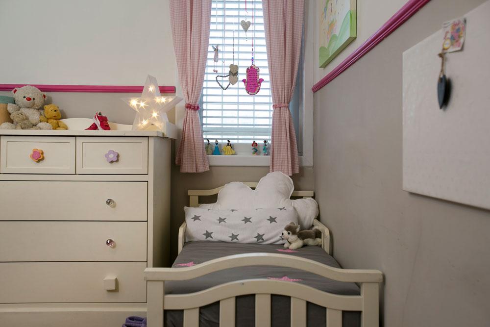 בחדרן של שתי הבנות הקטנות לא נעשו שינויים משמעותיים, מלבד צביעת הקירות והדבקת קרניז ורוד. החדר קושט בווילונות בדוגמת פפיטה, וביניהם נתלו חפצי חן (צילום: שירן כרמל)