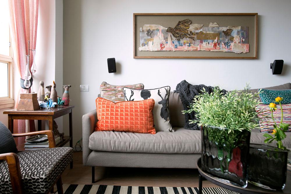 הסלון עשיר בטקסטיל במרקמים ובצבעים שונים. על השולחן שניצב בין הספה לכורסה יש אוסף בובות תפורות של timo. עבודת האמנות שתלויה מעל הספה הוזמנה מאמן הגרפיטי dede (צילום: שירן כרמל)
