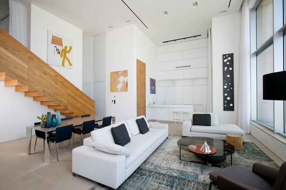 הסלון והמטבח מתנשאים לגובה שתי קומות. על הקירות עבודות אמנות של ציירים כמו יאיר גרבוז, פנחס כהן גן ודוד ריב. כולן נקנו בגלריה נעמי גבעון (צילום: שירן כרמל)