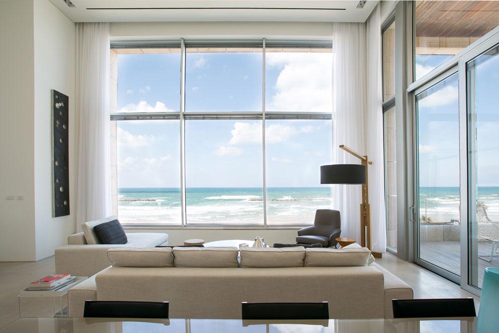 סלון הדופלקס ששיפוצו ועיצובו הושלמו זה לא מכבר. חלונות המסך העצומים מטעים לחשוב שהדירה נמצאת ממש על החוף (למעשה, כביש מפריד בינו לבין הבניין) (צילום: שירן כרמל)