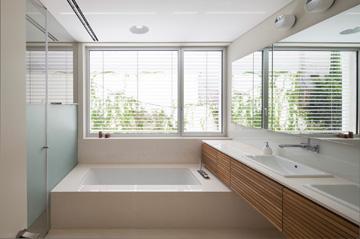 חדר הרחצה של ההורים: ריצוף האבן עולה ומכסה את האמבטיה ואת אדן החלון (צילום: עמית גרון)