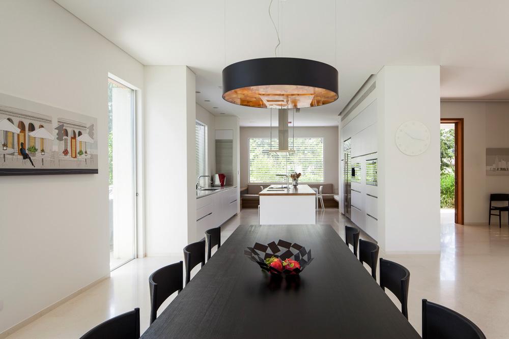 בצד השני של המטבח יש שולחן קטן לארוחות יומיומיות, פינת מחשב וספת רביצה שמעליה חלון רחב. מימין נראית דלת הכניסה (צילום: עמית גרון)