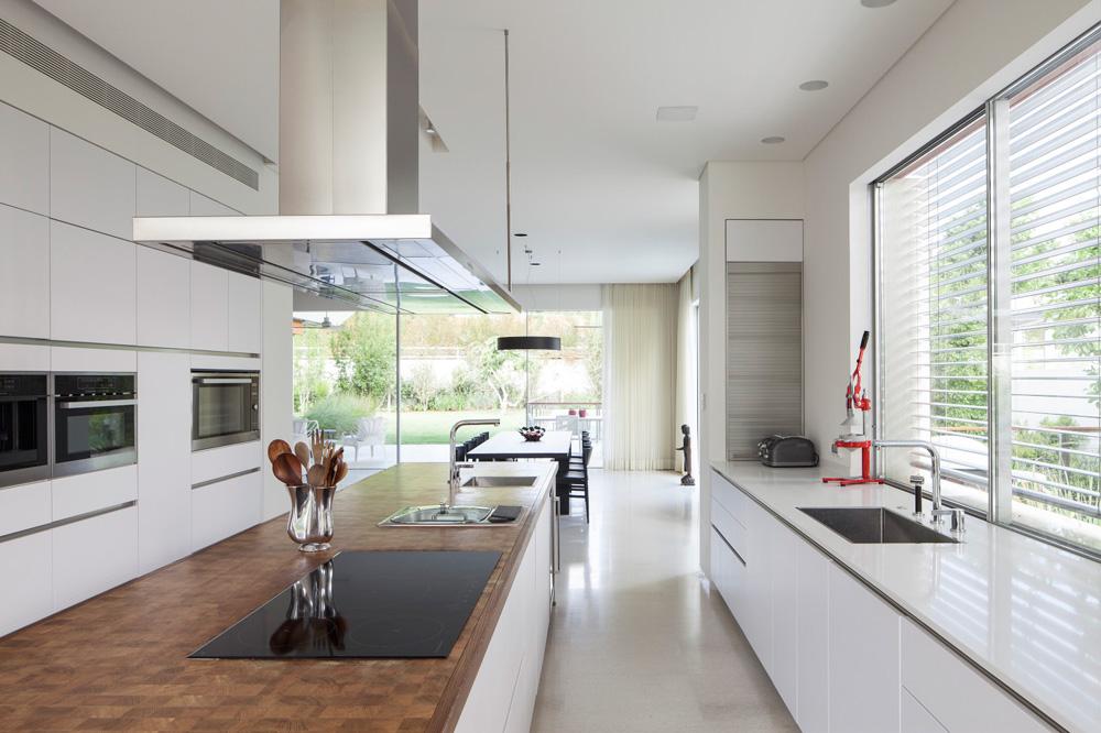 משני צידי המטבח תוכננו פינות אוכל. כאן נראה השולחן הרשמי יותר, שפונה אל הסלון והבריכה (צילום: עמית גרון)