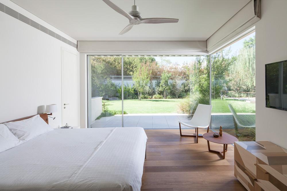 חדר ההורים נהנה מקירות זכוכית שפונים לגינה ומוצלים באמצעות וילונות רומאיים. משני צדי המיטה דלתות במישור הקיר: האחת מובילה לחדר ארונות, והאחרת לחדר רחצה (צילום: עמית גרון)