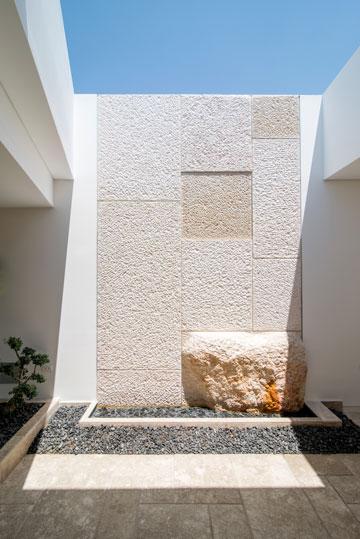 המבואה בקומה העליונה מזכירה חצר פנימית, עם קיר אבן וחלון סקיילייט שנפתח בלחיצת כפתור (צילום: אילן נחום)