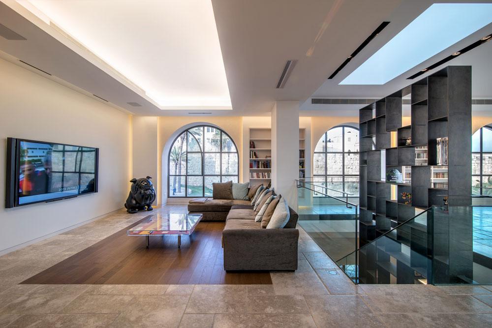 באמצע הסלון תוכנן גרם מדרגות (יש בבית שניים), שמוביל לקומת גלריה ולקומת הרחוב, ומלווה לכל גובהו בספריית ברזל. בסלון יש שתי פינות ישיבה, אחת מול ספרייה והשנייה מול מסך הטלוויזיה (צילום: אילן נחום)