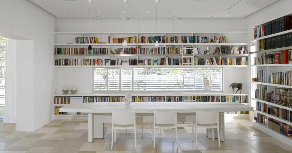בפינת האוכל שולחן חגיגי, ארוך ולבן, מוקף ספרייה גדולה. חלון ארוך וצר נפער לרוחב הקיר, במקביל לשולחן. שטח ה''מלבן'' המשמש את המטבח ופינת האוכל המשותפים - כמאה מ''ר (צילום: עמית גרון)