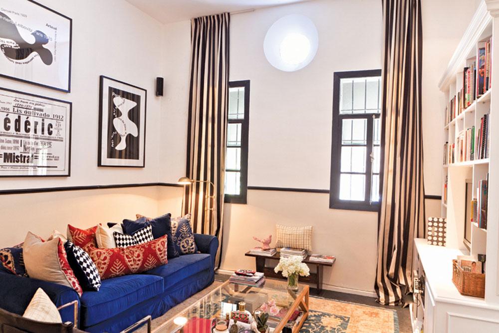 בעקבות אריחי הריצוף השחורים שהיו בבית נבחר הצבע השחור גם לפרטים נוספים, למשל חלונות העץ והקרניז המחלק את הקיר לשניים. מבט לסלון (צילום: אבישי פינקלשטיין)