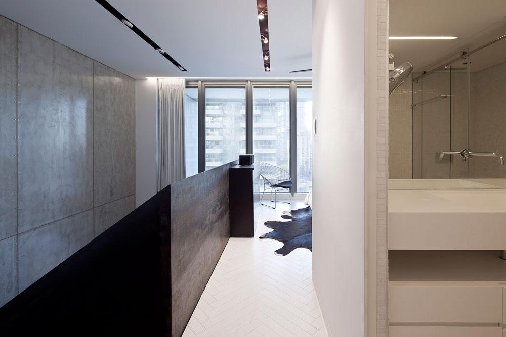 מבט מישורת המדרגות לכיוון חדר ההורים בגלריה. המעקה עשוי ברזל אטום גם כדי להסתיר את המיטה מעיני מי שנמצא למטה (צילום: עמית גרון)