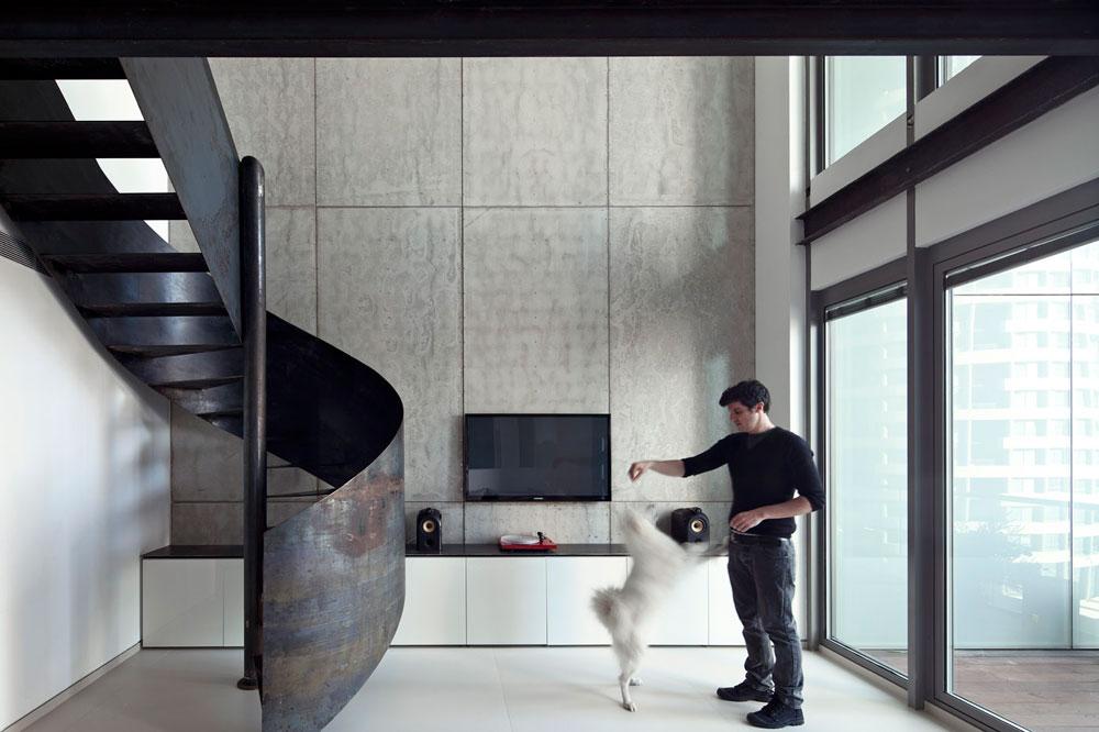 הקיר המרכזי בחלל מתנשא לגובה שתי הקומות, וכוסה בלוחות בטון עם סיבי זכוכית. ''הלוחות נחשבים למוצר זול יחסית, מקביל במחירו למחיר עבודת גבס למ''ר. העובדה שאין צורך בעבודות גמר כמו שפכטל וצבע הפכה את הקיר הזה לאלמנט הכי זול בדירה'', מסביר האדריכל דין גרסטנר. לרוחב הקיר נמתחה שידה נמוכה מ''איקאה'', שעליה הונחה פלטת ברזל חתוכה (צילום: עמית גרון)