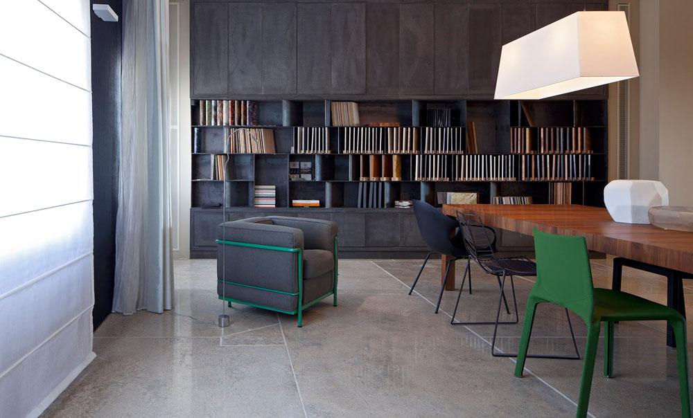 """שולחנות עבודה גדולים, מוקפים ספריות חומרים וקטלוגים. הרצפה חופתה לוחות של אבן קרינה והספרייה נבנתה בידי שלושה אנשי מקצוע - נגר, מסגר (""""adam-team"""") ויבואן האבן. על השולחן קערות מזכוכית מותזת, ולצדו כסאות מעצבים וכורסה של לה-קורבוזיה (כל הפריטים מ''טולמנ'ס''). מעל גוף תאורה של מרסל ואנדרס, ווילונות (''רנבי'') מרככים את האור שחודר דרך החלונות (יאלו) (צילום: עמית גרון)"""
