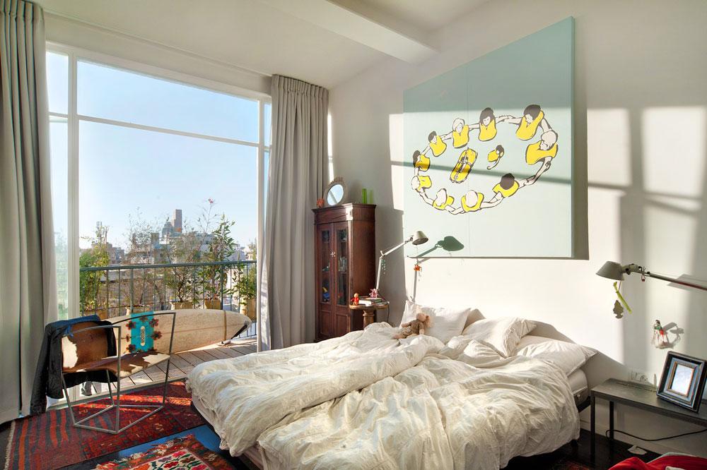 חדר השינה של אילון: רהיטים מדירתו הקודמת, תמונה שצייר ומרפסת קטנה. הוא מחכה לכרכוב שפורק מבית ברומניה, וישמש כראש למיטה (צילום: עמרי אמסלם)