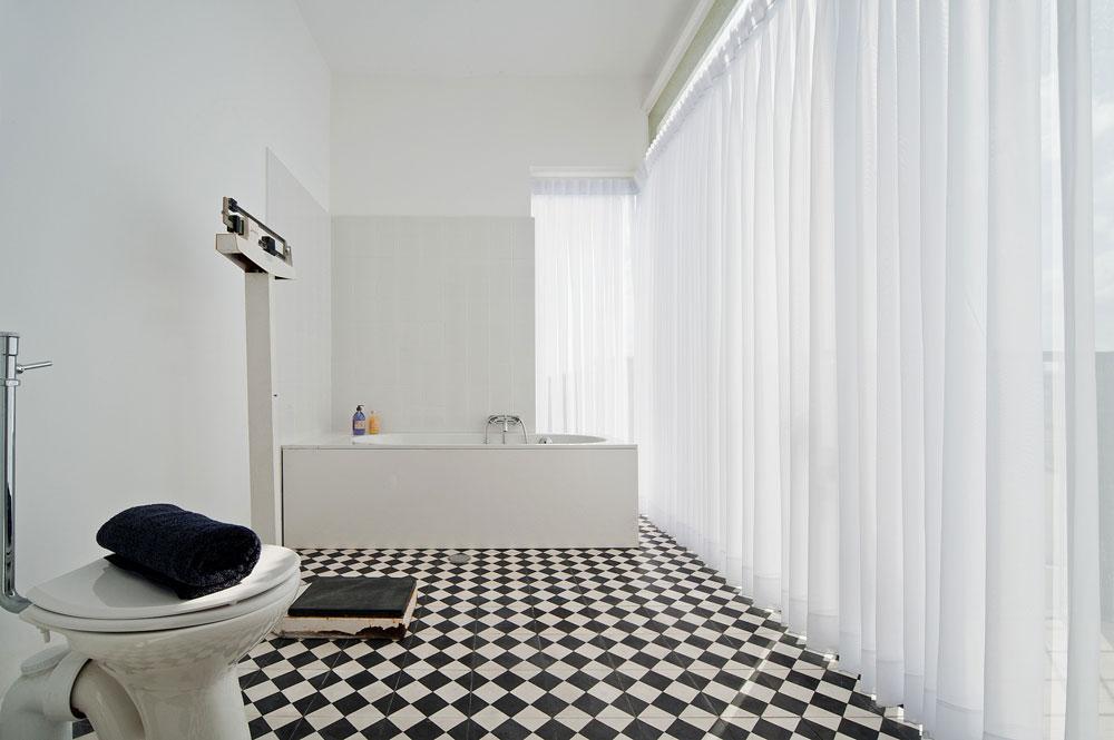 לחדר השינה צמוד חדר רחצה עצום, עם חלון שנמתח מהתקרה לרצפה. כמו כל חדרי הרחצה בבית, הוא רוצף באריחים בדוגמת שח-מט בשחור-לבן (צילום: עמרי אמסלם)