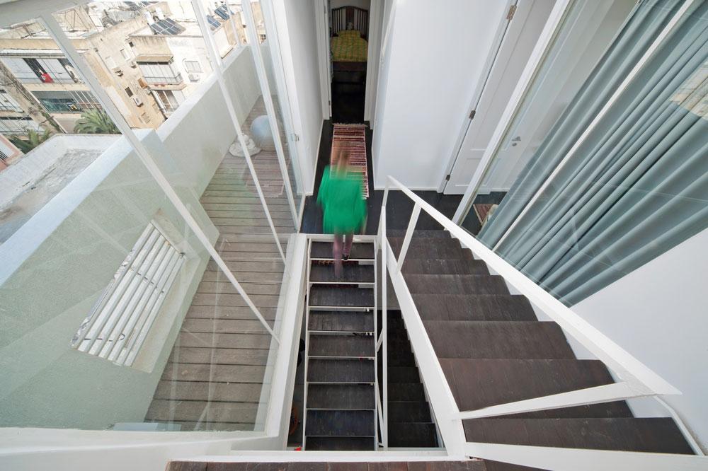 מבט מהמפלס העליון והאחרון של הדירה, שכולו מרפסת, אל מפלס חדרי הילדים. מימין חדרה של הבת, מלפנים חדרו של הבן, שבו מיטה שבנה אילון כשהיה בן 15 (צילום: עמרי אמסלם)
