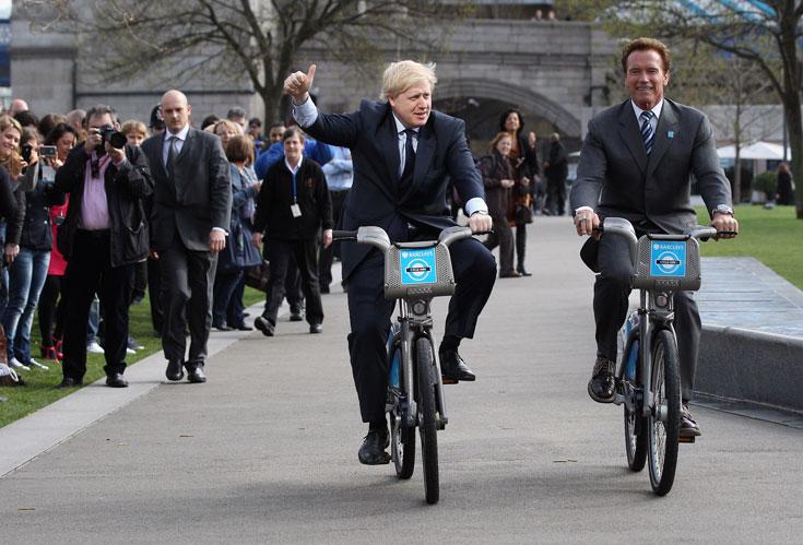 """גם תיירים יכולים לשכור אופניים. ראש עיריית לונדון בוריס ג'ונסון מדווש עם ידיד מחו""""ל (צילום: gettyimages)"""