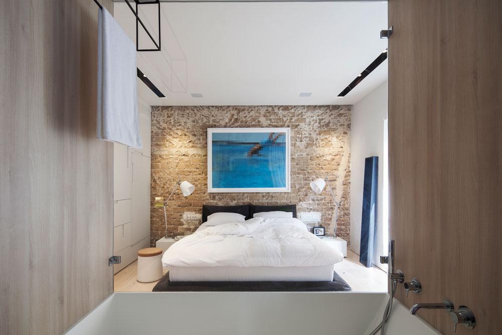 מבט מתוך חדר הרחצה אל חדר השינה. קיר זכוכית מפריד ביניהם, ויוצר אשליה של מרחב מפנק, גדול ומשותף (צילום: אביעד בר נס)