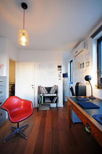 הסטודיו של כנפו על הגג. שולחן עבודה אנגלי מהמאה ה-19 וכיסא אימס מפיברגלס וריפוד פלסטי אדום (צילום: נעמה כנפו)