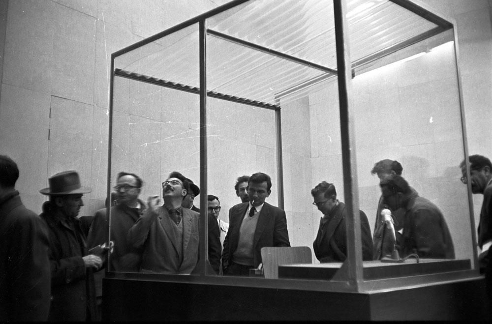 בוחנים את תא הזכוכית שבו ישב הנאשם. מנהל הבמה הסמוי, כתבה חנה ארנדט, היה בן גוריון בעצמו (צילום: דוד רובינגר)