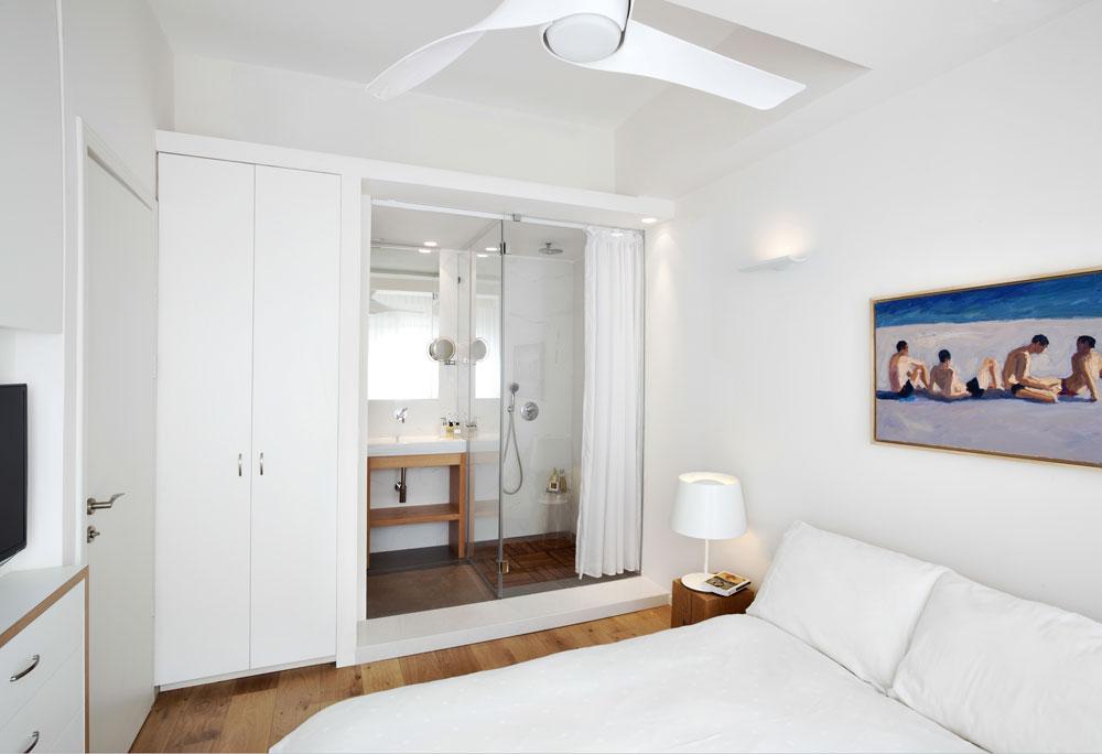 לצד המיטה בחדר השינה עובה הקיר ומדרגה מפרידה בין מפלס המיטה ליחידת רחצה צמודה. מעל המיטה ציור של עומר לוגאנג, שנקנה בצרפת (צילום: אורי אקרמן)