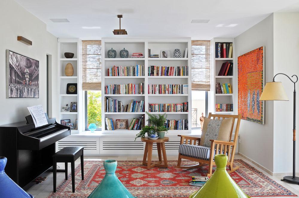 צד אחד של הסלון מוקדש לקריאה וכולל ספרייה ענקית, כיסא נדנדה וגם פסנתר  (צילום: שי אדם)