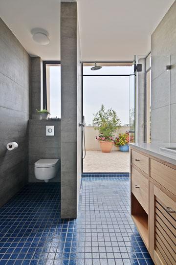"""חדר  הרחצה של ההורים מרוצף באריחי גרניט פורצלן כחולים בגוון שהמעצבת מכנה """"אוקיינוס עמוק"""" (צילום: שי אדם)"""