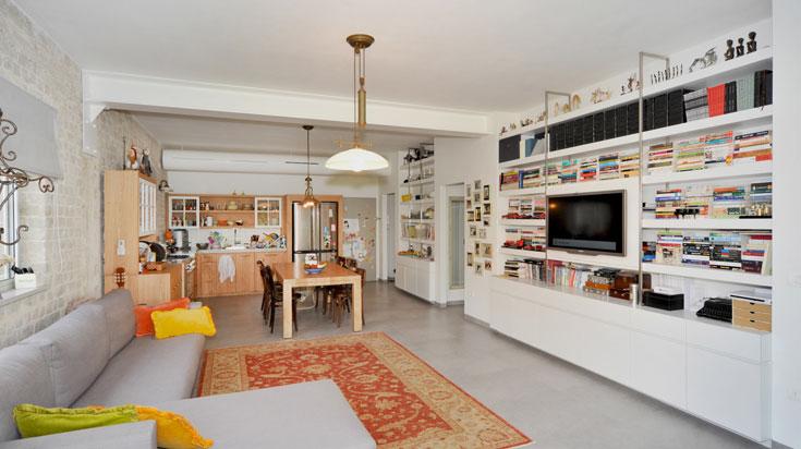 הקיר המרכזי והעבה ''סופג'' את חללי האחסון של הדירה: ספרייה מצד הסלון, ארונות מצד חדרי השינה (צילום: עמרי אמסלם)