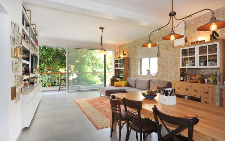 חלל הסלון והמטבח - מלבן ישר קווים ופתוח לחלוטין - מעוצב בסגנון חם, עם קיר לבני סיליקט שנחשפו בשיפוץ ומטבח מעץ אלון מבוקע (צילום: עמרי אמסלם)