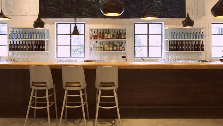 מעל הבר נתלו מנורות בעיצוב טום דיקסון. המשקאות והכלים מוצגים בארונות פתוחים שעשויים ברזל צבוע לבן (צילום: עמית גרון)