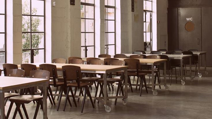 כסאות שונים מקיפים את השולחנות, חלקם פשוטים מאוד, במראה שמזכיר כסאות בית ספר (צילום: עמית גרון)