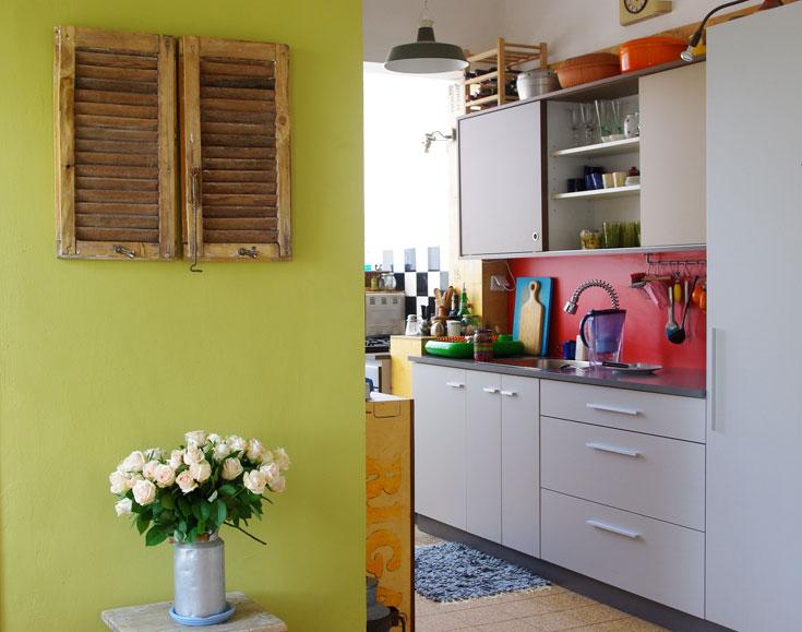 ארונות המטבח, משטח העבודה וחיפוי הקיר עשויים פורמייקה בגוונים שונים. מולם משטח עבודה נוסף, שנבנה משאריות של חומרי אריזה (צילום: אמיר רווה)