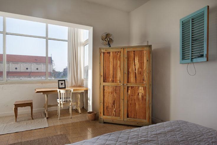 הארון עשוי עץ אורן ודלתות מאריזות של חבילות דיקט. מעל המיטה תריס נוסף שנמצא ברחוב, נצבע והפך למעמד לטלפון (צילום: אסף פינצ'וק)