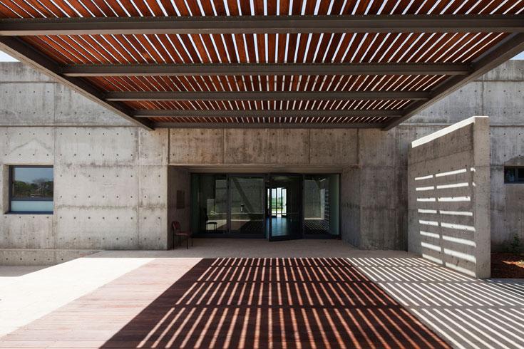 מעברים מוצללים מהשמש. המבנה כולו משלב בטון חשוף עם עץ (צילום: אביעד בר נס)