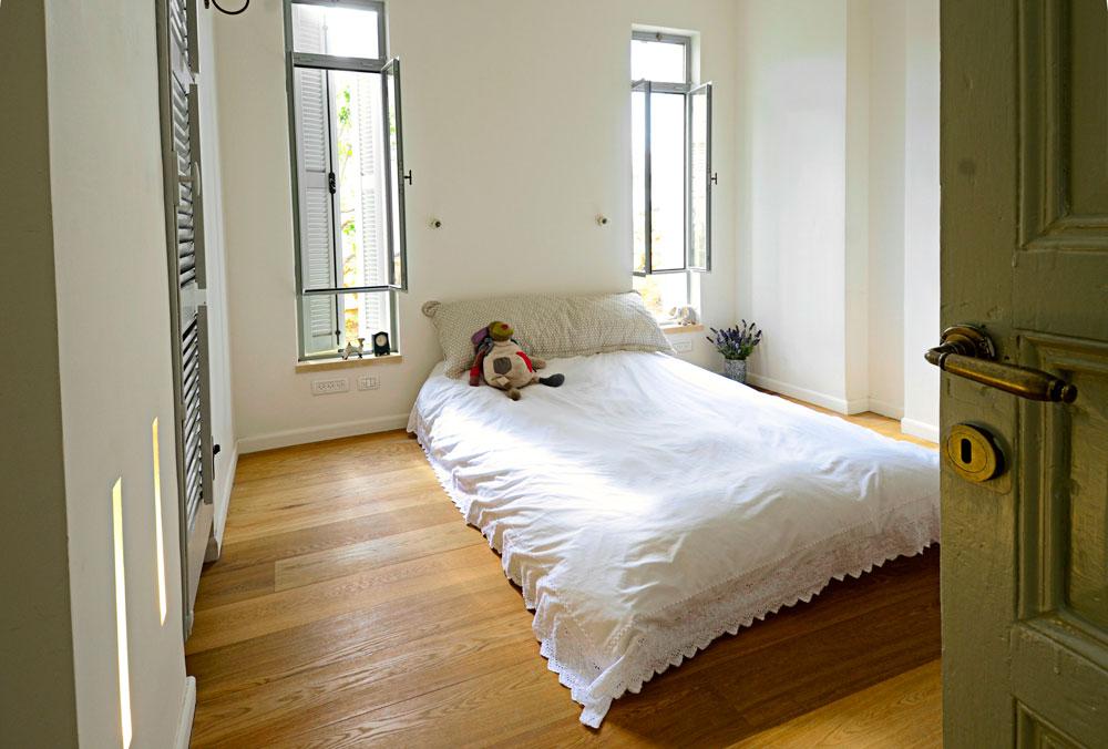 חדר השינה של ההורים לא גדול מספיק כדי להכיל גם שידות צד. לכן הוחלט להשתמש באדני החלון הנמוכים כמדפים לצד המיטה. חדר הארונות סגור בדלת תריס ישן, משוק הפשפשים (צילום: הילה גיא)