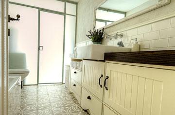 דלת מזכוכית חלבית מפרידה בין חדר הרחצה לחדר הכביסה, כדי להכניס פנימה אור יום (צילום: הילה גיא)