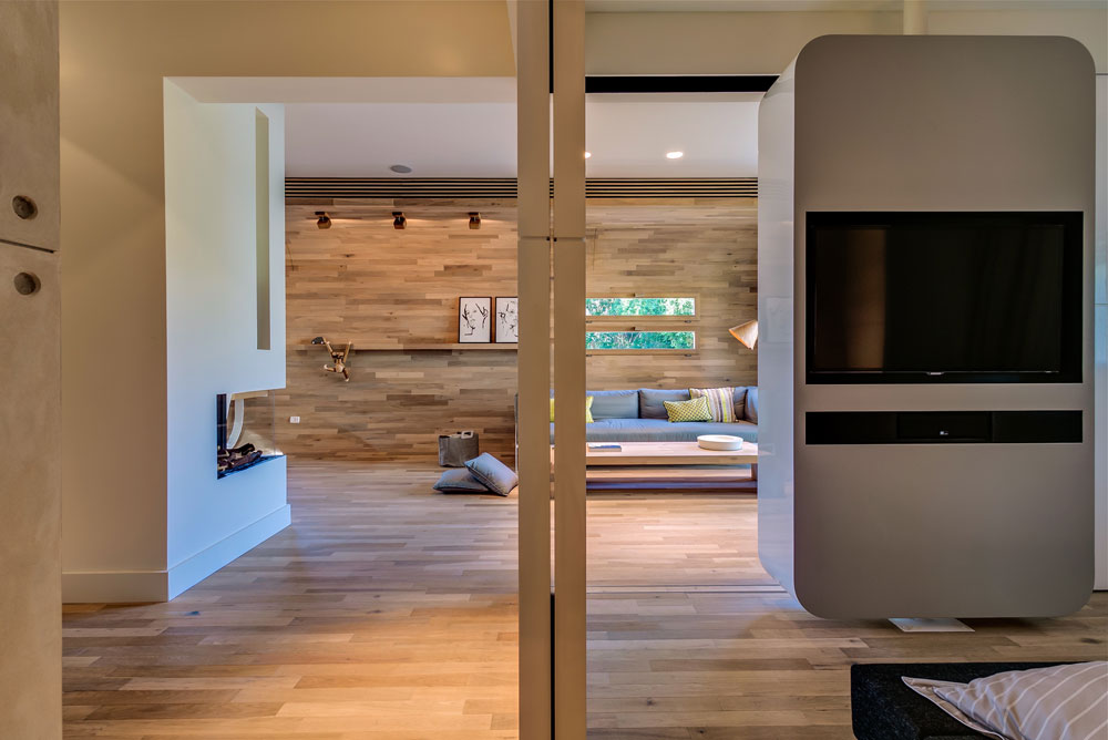 מבט מכיוון דלת הכניסה: מימין חדר השינה, שקירותיו נעים על מסילות ומאפשרים פתיחות או פרטיות, לפי הצורך. משמאל חדר הרחצה וממול, לאורך כל הדירה, חלל הסלון והמטבח (צילום: איתי סיקולסקי)