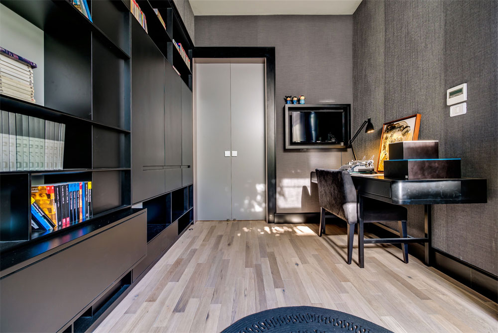 חדר העבודה כהה ודרמטי, עם לוחות זכוכית בגוון ברונזה שמחפים את הקיר, ארונות ורהיטים שחורים (צילום: איתי סיקולסקי)