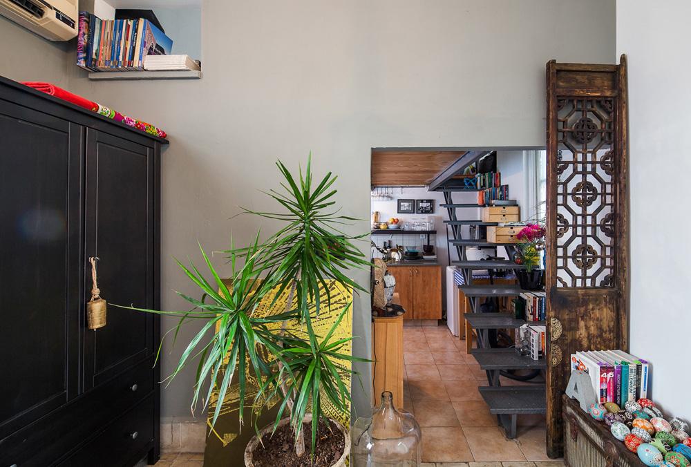 מבט מהסלון לכיוון המטבח והעלייה לגלריית השינה. ''חשוב שהעין תמצא עניין, שתעצור בסקרנות סביב חפצים מסוימים. גם דברים קטנים יכולים להיות משמעותיים: ידית מיוחדת לארון, למשל'' (צילום: טל ניסים)