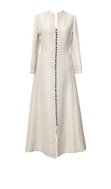 """שמלת כלה לבנה עם כפתורים לכל אורכה, 1972. """"שמלה מבד אריג צמר עם חוטי לורקס, שנעשתה על ידי משפחת קאשי. מאחורי הבד הזה יש סיפור מיוחד מאוד"""" (צילום: ענבל מרמרי)"""