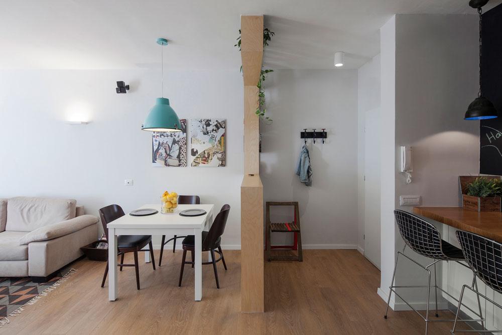 הרהיט מסתיר את מתלה המעילים שבמבואה. מצדו השני שולחן אוכל נפתח מ''איקאה'', כסאות רטרו שחורים, מנורה לבנה שנצבעה טורקיז והדפסים שיצרו המעצבים בסגנון יפני (צילום: אביעד בר נס)