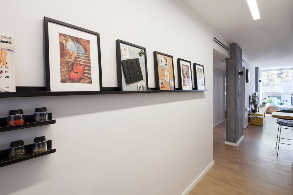 על קיר המטבח מדפי פח צרים, שעליהם הונחו מסגרות שחורות זהות, שבכל אחת מהן משהו אחר: הדפס, לוח מגנטי, לוח שעם וקולאז' תבלינים (צילום: אביעד בר נס)
