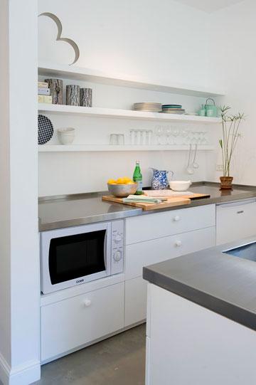 המטבח כולל שני פסי ארונות נמוכים ומעליהם משטחי עבודה מנירוסטה. מדפי עץ לבנים מוסיפים מקום אחסון (צילום: גלית דויטש)