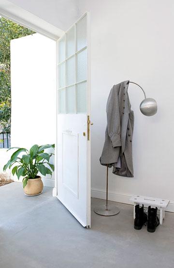 מבואה עם עציץ לפני הדלת, ובפנים מנורה מתוך אוסף פרטי של הבעלים. הרצפה חופתה בבטון דק, אפור בהיר (צילום: גלית דויטש)